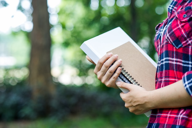 Jeune fille embrasse son livre dans la jungle verte Photo Premium
