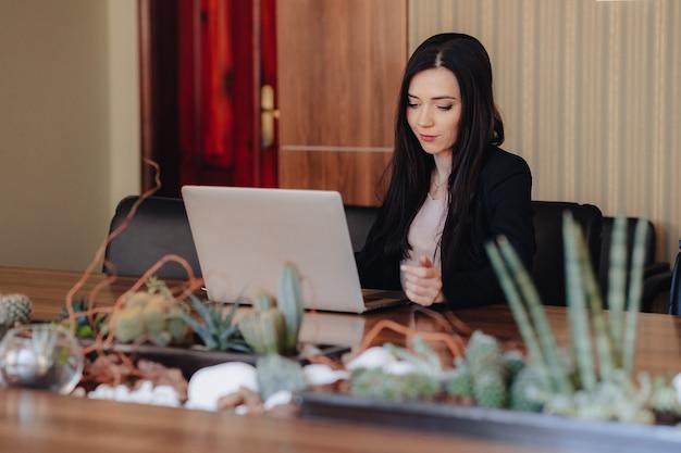 Jeune fille émotive attrayante dans les vêtements de style d'affaires assis à un bureau sur un ordinateur portable et un téléphone dans le bureau ou l'auditorium Photo Premium