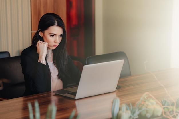Jeune fille émotive attrayante dans les vêtements de style d'affaires assis à un bureau sur un ordinateur portable et téléphone Photo Premium