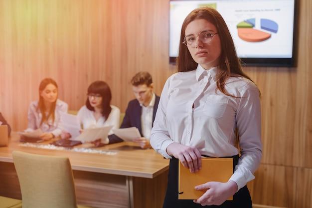 Jeune fille employée de bureau élégant attrayant dans des verres avec un ordinateur portable dans les mains sur fond de collègues de travail Photo Premium