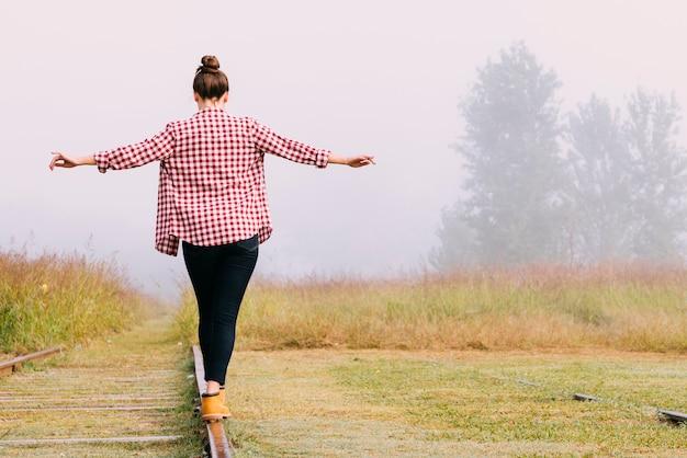 Jeune fille en équilibre sur le chemin de fer Photo gratuit