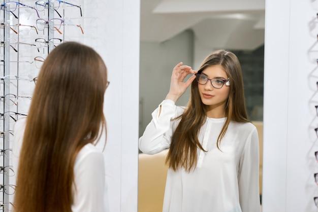 Jeune fille essayant des lunettes devant le miroir. Photo Premium