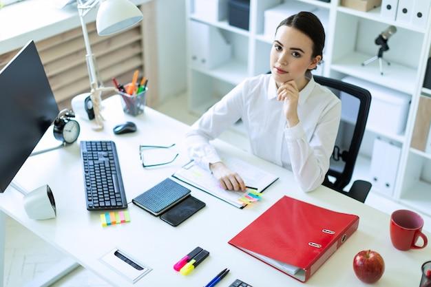 Une jeune fille est assise au bureau de l'ordinateur dans le bureau. Photo Premium