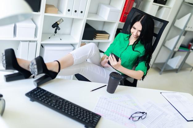 Une Jeune Fille Est Assise Dans Le Bureau, A Jeté Ses Jambes Sur La Table Et Tient Le Téléphone Dans Ses Mains. Photo Premium