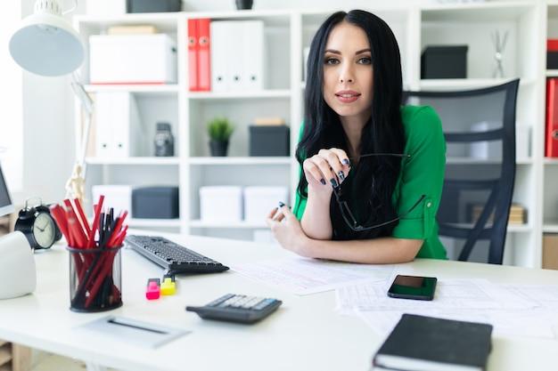 Une Jeune Fille Est Assise Dans Le Bureau à La Table Et Tient Des Lunettes Dans Ses Mains. Photo Premium