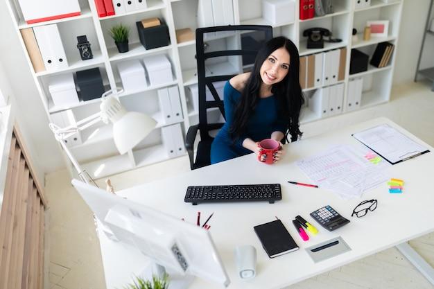 Une jeune fille est assise dans le bureau à la table et tient une tasse rouge dans ses mains Photo Premium