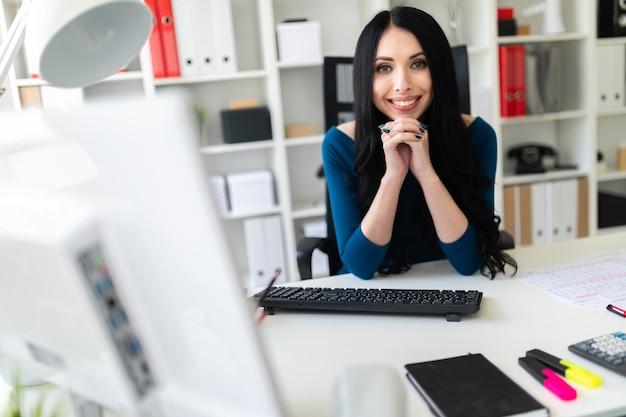 Une jeune fille est assise dans le bureau à la table. Photo Premium