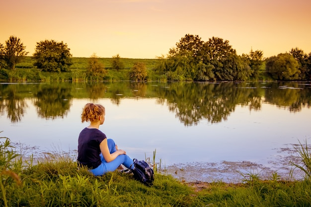 Une Jeune Fille Est Assise Sur La Rive Et Admire La Nature Pendant Le Coucher Du Soleil. Mode De Vie Sain, Rester Dans La Nature Photo Premium