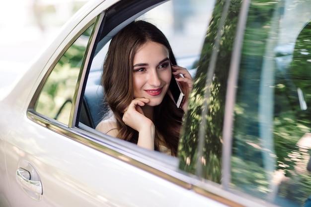 Une Jeune Fille Est Assise Sur Le Siège Arrière D'une Voiture Et Parle Au Téléphone. Photo Premium