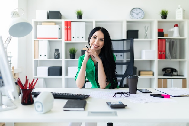 Une Jeune Fille Est Assise à La Table Du Bureau Et Tient Un Crayon Dans Ses Mains. Photo Premium
