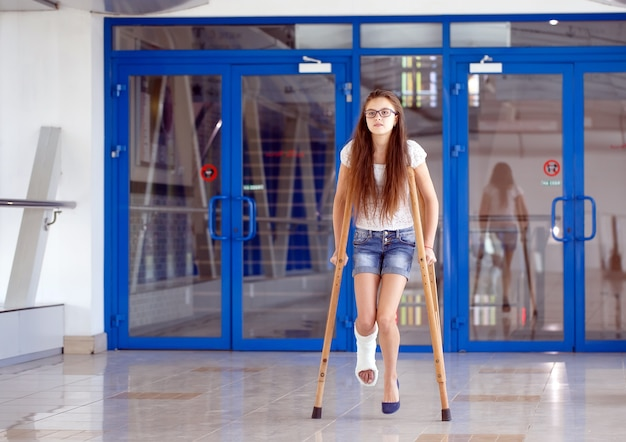 Une jeune fille est sur des béquilles dans le couloir de l'hôpital. Photo Premium