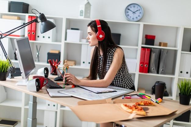Une jeune fille est debout près d'une table, tenant un marqueur vert et regardant l'écran. avant la fille sur la table se trouve un tableau magnétique. sur la tête de la fille portant des écouteurs. Photo Premium