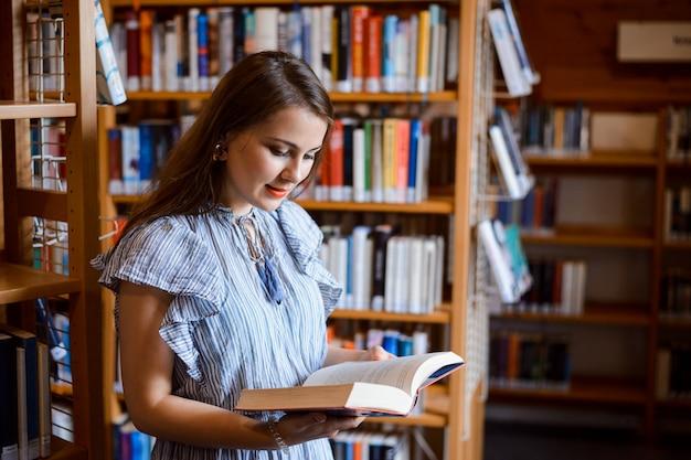 Jeune Fille étudiante Intelligente Lecture Livre Dans La Bibliothèque Photo Premium