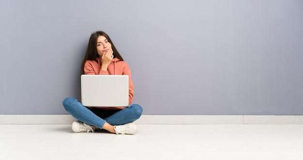Jeune fille étudiante avec un ordinateur portable sur le sol, pensant à une idée Photo Premium