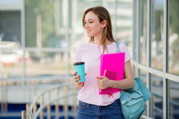 Jeune fille étudiante avec une tasse de café dans la rue Photo Premium