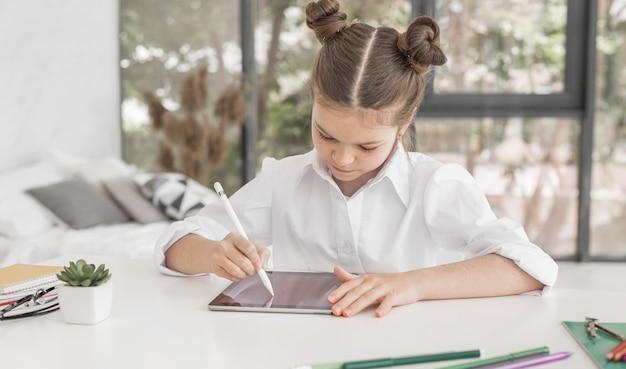 Jeune Fille étudie Sur Tablette Avec Stylo Photo gratuit
