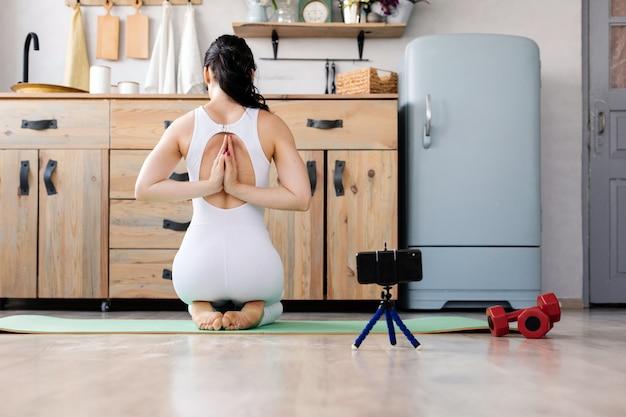Jeune fille faisant du yoga à la maison Photo Premium