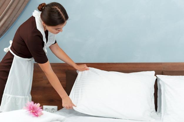 Jeune fille faisant le lit dans la chambre d'hôtel Photo Premium