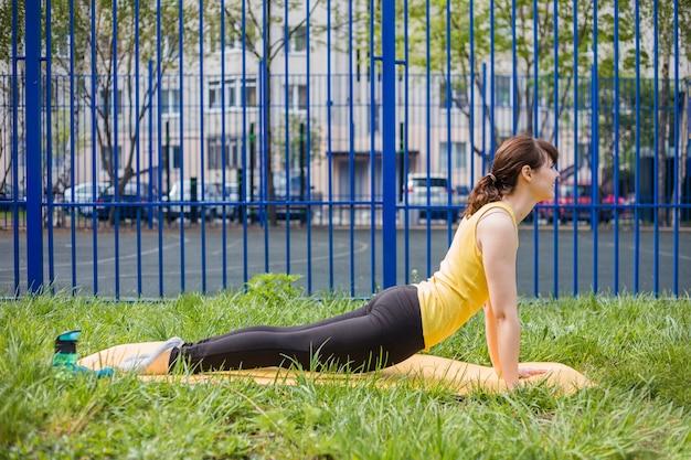 Une Jeune Fille Fait Du Sport Sur Un Tapis. Une Jolie Fille En Uniforme De Sport Effectue Des Exercices Dans La Rue. Photo Premium