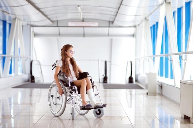Une jeune fille en fauteuil roulant se tient dans le couloir de l'hôpital. Photo Premium