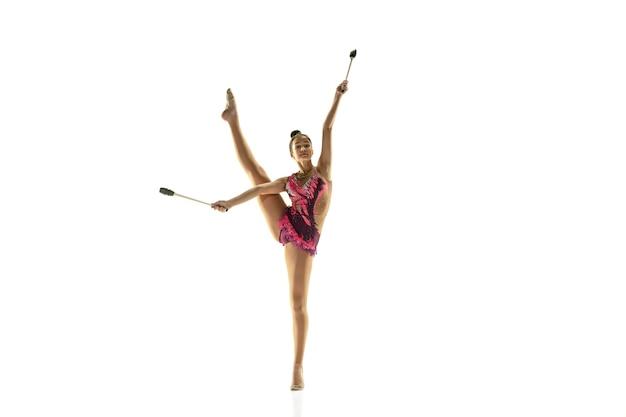Jeune Fille Flexible Isolée Sur Un Mur Blanc. Modèle Féminin Adolescent En Tant Qu'artiste De Gymnastique Rythmique Pratiquant Avec De L'équipement. Exercices Pour La Flexibilité, L'équilibre. Grâce En Mouvement, Sport. Photo gratuit