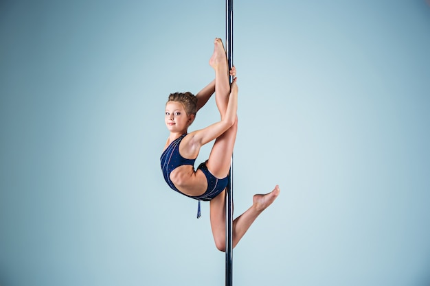 La Jeune Fille Forte Et Gracieuse Effectuant Des Exercices Acrobatiques Sur Pylône Photo gratuit