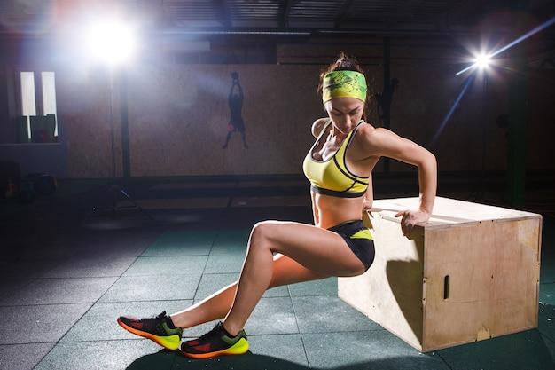 Jeune fille forte et musclée saute dans la salle de sport à l'élévation. entraînement des jambes et cardio Photo Premium