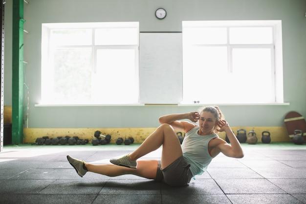 Jeune fille forte et souriante faisant des exercices pour les muscles de l'estomac, appuyez au sol dans la spore Photo Premium