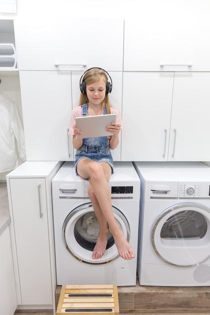 Une jeune fille heureuse écoute de la musique sur un casque, tenant une tablette dans la buanderie avec machine à laver Photo Premium