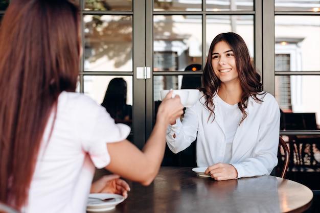 Une Jeune Fille Heureuse Et Sa Petite Amie Font Tinter Les Tasses. Ils Sont Assis Dans Le Café. Vue à La Première Personne. Photo Premium