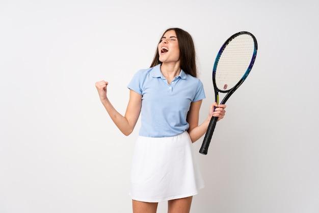 Jeune fille, sur, isolé, mur blanc, jouer tennis, et, célébrer, a, victoire Photo Premium