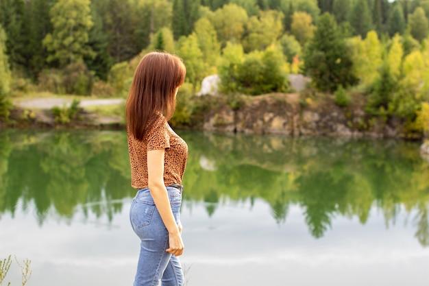Jeune Fille En Jeans Se Promène Près D'un Beau Lac Par Temps Nuageux. Photo Premium