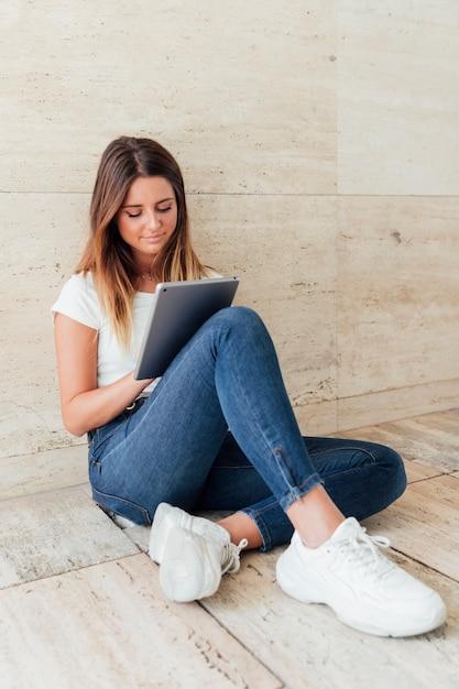 Jeune fille en jeans avec une tablette Photo gratuit