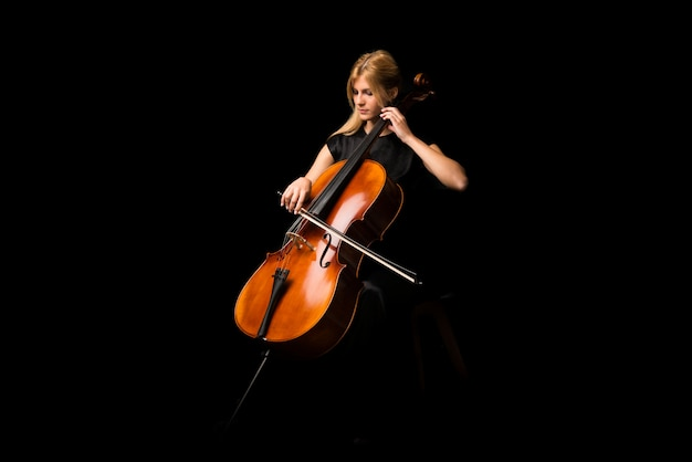 Jeune fille jouant du violoncelle sur fond noir isolé Photo Premium