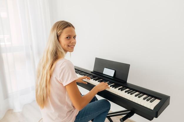 Jeune Fille Jouant De L'instrument à Clavier à La Maison Photo gratuit