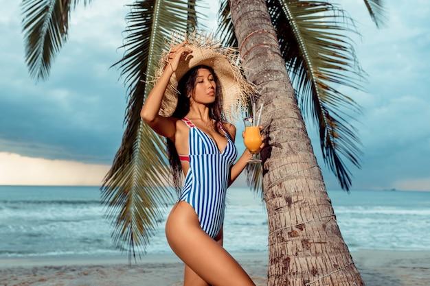 Une jeune fille de luxe dans un bikini et un chapeau de paille est debout avec un verre de jus d'orange sous un palmier sur une plage tropicale. Photo Premium