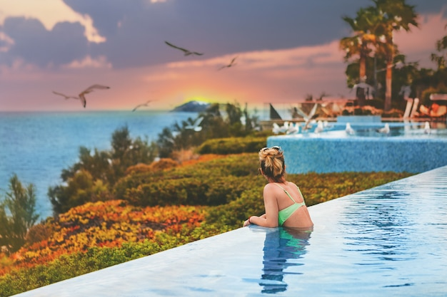La jeune fille en maillot de bain dans la piscine en regardant le coucher de soleil à la mer. vue arrière, style de vie Photo Premium