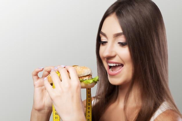 Une Jeune Fille Mange Un Hamburger Et Songe à Un Régime. Minceur Réinitialisez L'excès De Poids. Le Concept De Santé Et De Beauté. Photo Premium