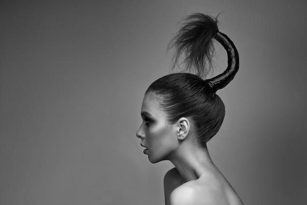 Une Jeune Fille Avec Un Maquillage Lumineux Et Une Peau Radieuse. Coiffure Créative Sur La Tête. Sur Un Gris. Photo Premium