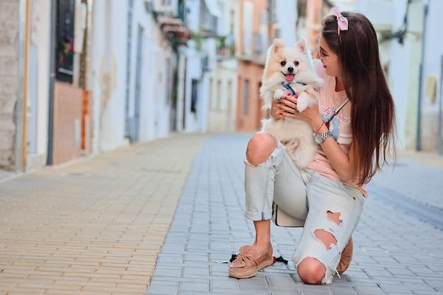 Jeune fille marchant avec son poméranien moelleux blanc. Photo Premium