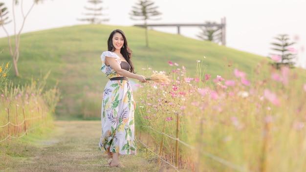 La jeune fille marche avec bonheur dans le jardin de fleurs dans la main tenant l'herbe Photo Premium