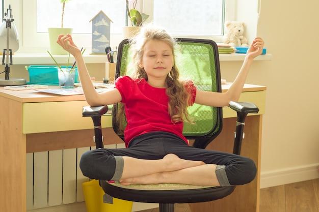 Jeune fille médite à la maison sur une chaise Photo Premium