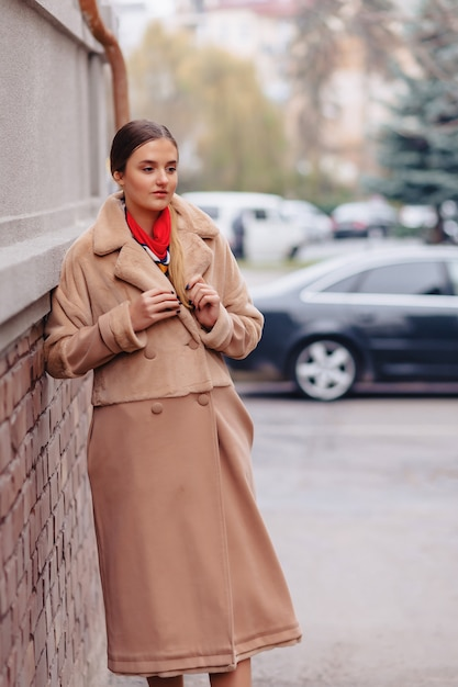 Jeune fille mignonne élégante dans un manteau de fourrure se promener dans la ville près des maisons en bois et des murs en pierre Photo Premium