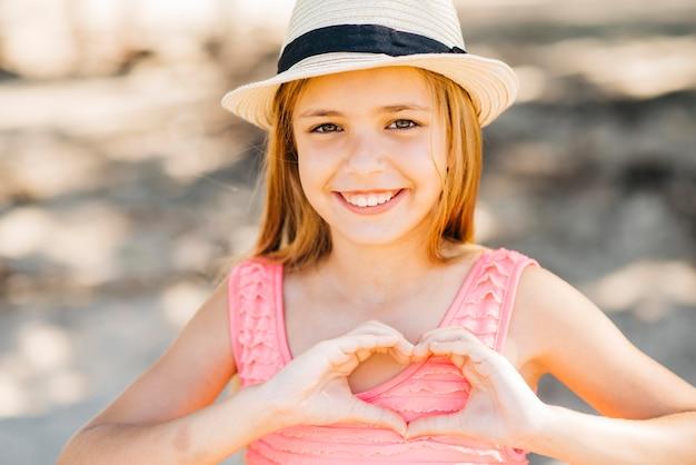 Jeune fille montrant le geste de l'amour et regardant la caméra sur la plage Photo gratuit