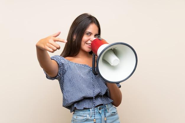 Jeune fille sur un mur isolé criant à travers un mégaphone Photo Premium