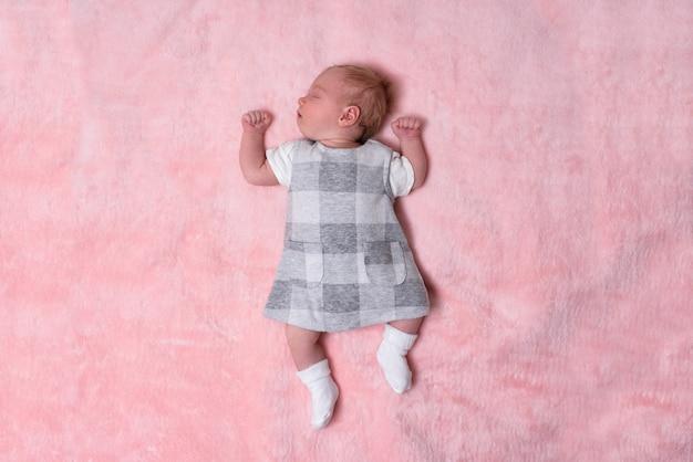 Jeune fille nouveau-née endormie vêtue d'une robe sur une couverture rose. vue de dessus. espace pour le texte Photo Premium