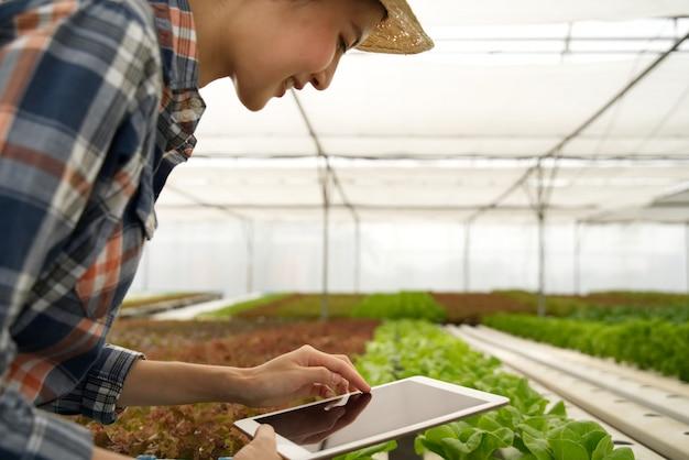 Jeune fille paysanne asiatique mignonne intelligente à l'aide d'une tablette pour vérifier la qualité et la quantité de légumes dans la ferme hydroponique Photo Premium