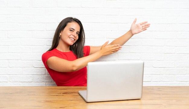 Jeune fille avec un pc dans une table, étendant les mains sur le côté pour inviter à venir Photo Premium