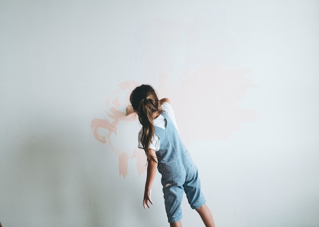 Jeune fille peindre les murs rose Photo Premium