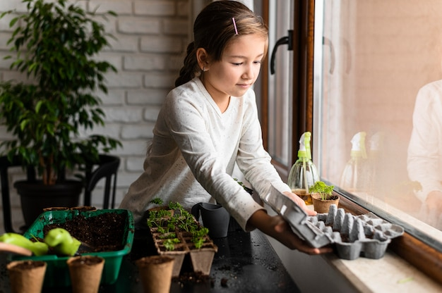 Jeune Fille Plantant Des Graines Par La Fenêtre Photo gratuit